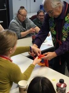 Dennis White demonstrates a round braiding technique to local educator Marci Erickson.