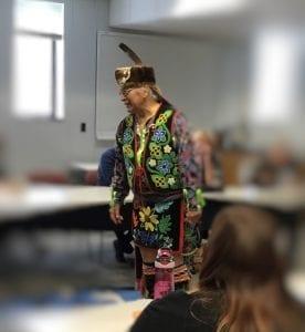Native elder Dennis White addresses room dressed in regalia.